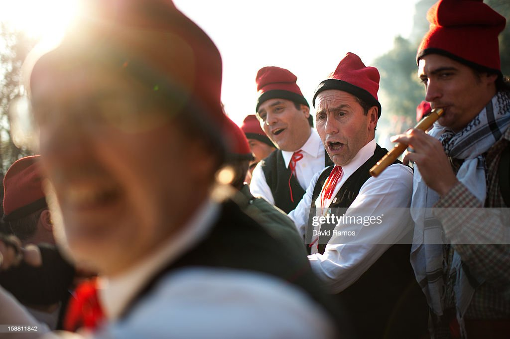 'Galejadors' sing as they pull a rope tied to the selected pine tree as it is felled during 'La Festa del Pi' (The Festival of the Pine) in the village of Centelles on December 30, 2012 in Barcelona, Spain. Early in the morning men and women born in Centelles, who are named 'Galejadors' wear their traditional costume with the Catalan red hat known as 'Barretina' and carry their shooting muskets as they walk into the forest to chop down a pine tree, load it on an ox cart and take it to the church in the village. There the pine tree is decorated with five bouquets of apples and wafers and hung inside a church until January 6. The tradition has been documented since 1751 and it is believed its origins are related to the trees and the pagan worship of fertilization related the winter solstice.
