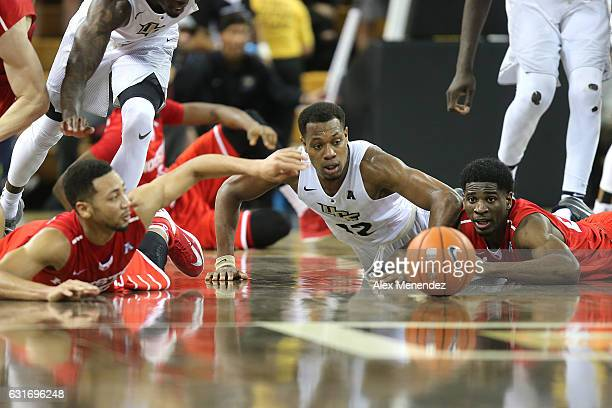 Galen Robinson Jr #25 of the Houston Cougars Matt Williams of the UCF Knights and Damyean Dotson of the Houston Cougars fight for a loose ball during...