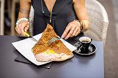 Traditional french pancake called galette cooked with buckweat and stuffed with cheese egg and ham on the restaurant table with coffee