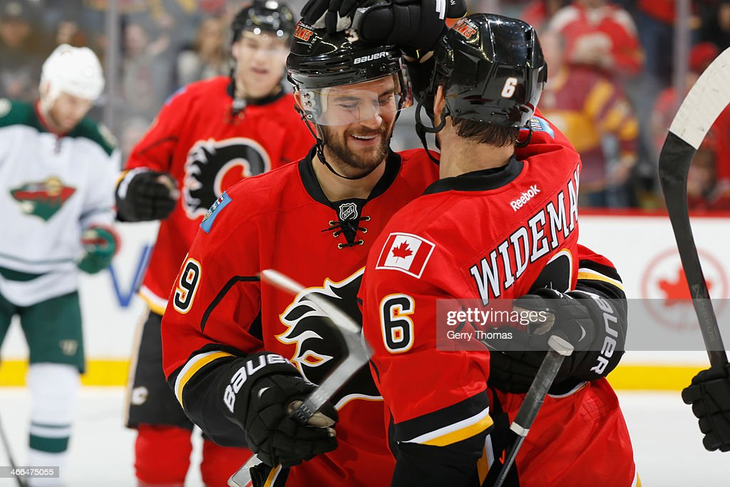 T.J. Galiardi #39 and Dennis Wideman #6 of the Calgary Flames celebrate a goal in game against the Minnesota Wild at Scotiabank Saddledome on February 1, 2014 in Calgary, Alberta, Canada.