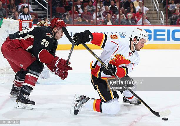 J Galiardi of the Calgary Flames handles the puck under pressure from Michael Stone of the Phoenix Coyotes during the second period of the NHL game...