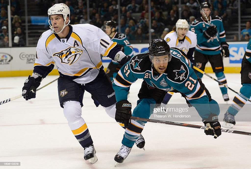 TJ Galiardi #21 of the San Jose Sharks gets checked from behind by David Legwand #11 of the Nashville Predators at HP Pavilion on February 2, 2013 in San Jose, California.