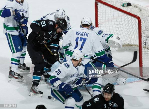 Galiardi of the San Jose Sharks looks for a rebound against Ryan Kesler Cory Schneider and Chris Higgins of the Vancouver Canucks in Game One of the...