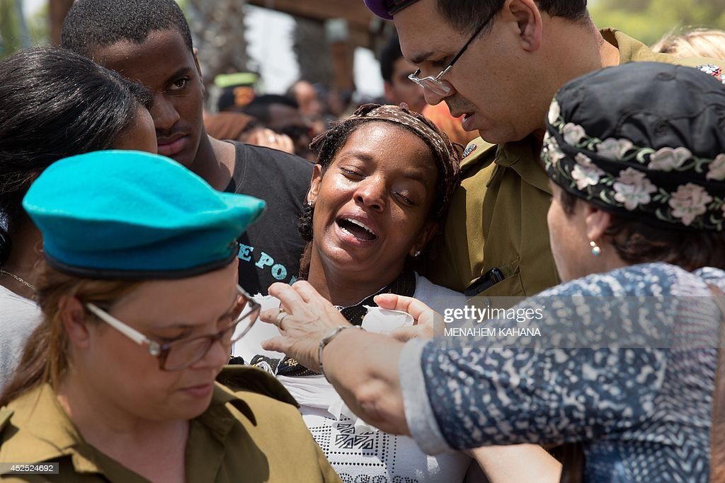 Galit the wife of 39yearold Israeli army tracker soldier Bansayan Kesahun is comforted during the funeral of her husband in the southern town of...