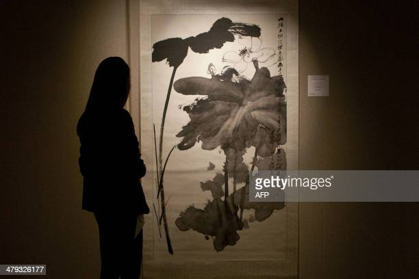 A gallerist stands in front of Chinese artist Zhang Daqian's 'Lotus in the Wind' scroll painting at the Sotherby's fine Chinese paintings spring sale...