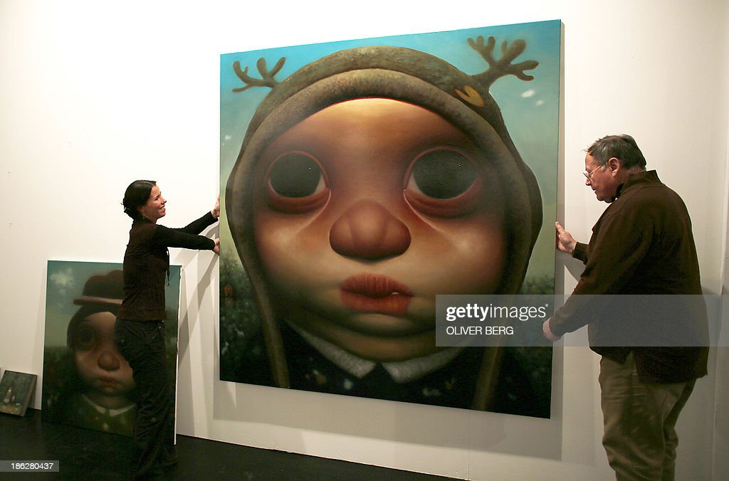 Gallerists hang the painting 'Taugenichts'(lit: good-for-nothing) by Young In Son at the booth of Galerie Maurer at Art.Fair in Cologne, Germany, on October 29, 2013. Art.Fair takes place from 31 October until 03 November 2013 in Cologne. AFP Photo /DPA/ OLIVER