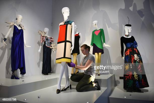 A gallery assistant adjusts a cocktail dress designed by French fashion designer Yves Saint Laurent in homage to Piet Mondrian at the Bowes Museum in...