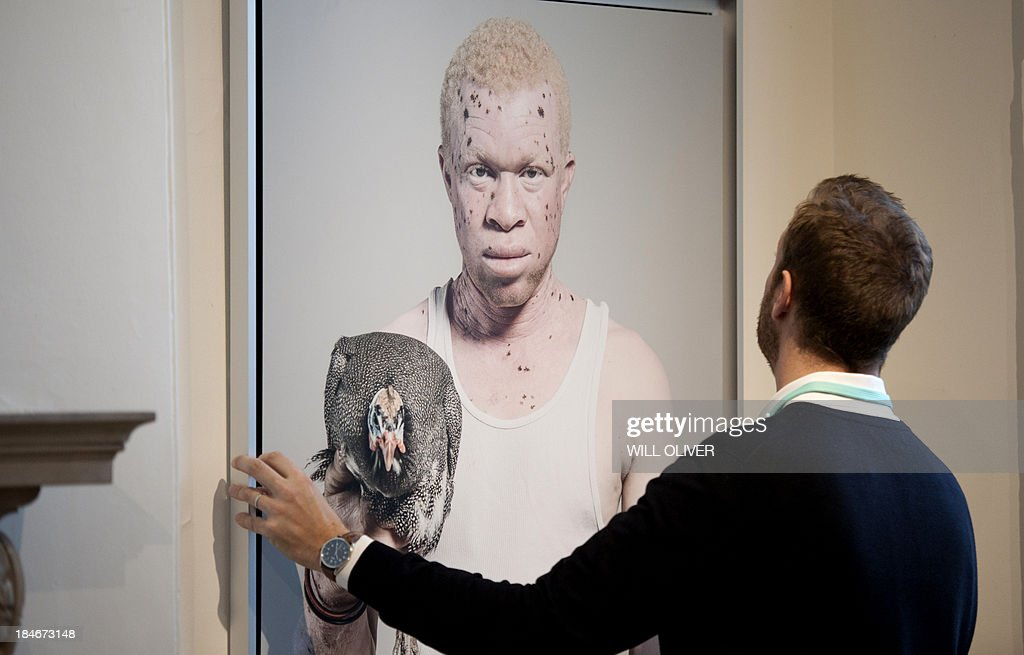 A gallery assistant adjusts a photograph by Senegalese artist Fabrice Monteiro titled 'Albinos' at the Contemporary African Arts Fair at Somerset House in Central London on October 15, 2013. The fair showcases emerging artists from Africa with a total of 70 artists from across the continent.