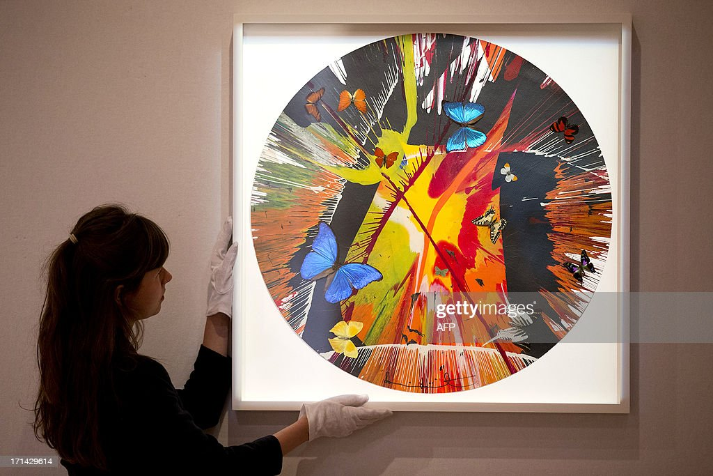 A gallery assistant adjusts 'Beautiful Cannibalistic Electrofetish Fighting in the Lava Beds Who Got My Eyeball? Paper Spin Painting (with butterflies)' by British artist Damien Hirst ahead of its sale at Bonhams auction house in London on June 24, 2013. AFP PHOTO/JUSTIN TALLIS == RESTRICTED TO EDITORIAL USE, MANDATORY MENTION OF THE ARTIST, TO ILLUSTRATE THE EVENT AS SPECIFIED IN THE CAPTION ==