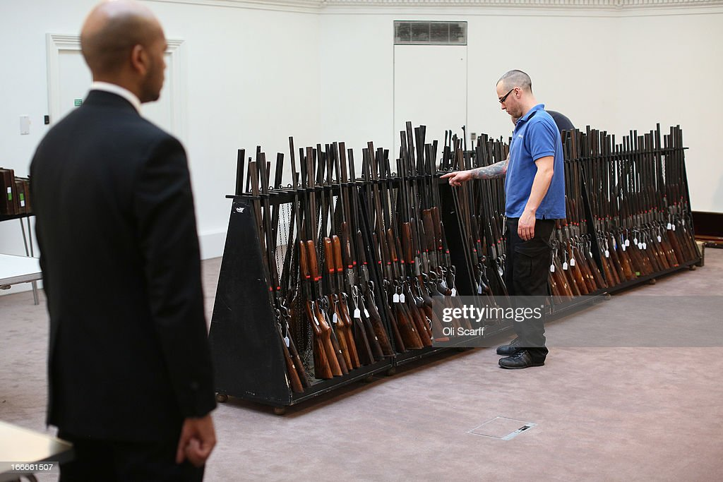 A gallery assistant arranges the firearms which are due to be auctioned on April 17, 2013 in the 'Fine Modern and Vintage Sporting Guns and Rifles' sale at Sotheby's, on April 15, 2013 in London, England. The sale features a gun that was presented to British Prime Minister Harold Macmillan by Russian President Nikita Krushchev during MacMillan's historic 1959 State Visit to Russia, it is expected to fetch 30,000 GBP.
