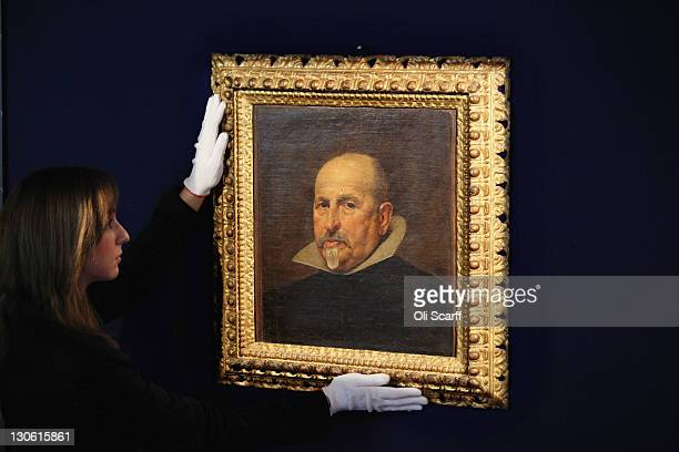 A gallery assistant at Bonhams auction house adjusts a newlydiscovered painting by Spanish artist Diego Rodriguez de Silva y Velazquez on October 27...