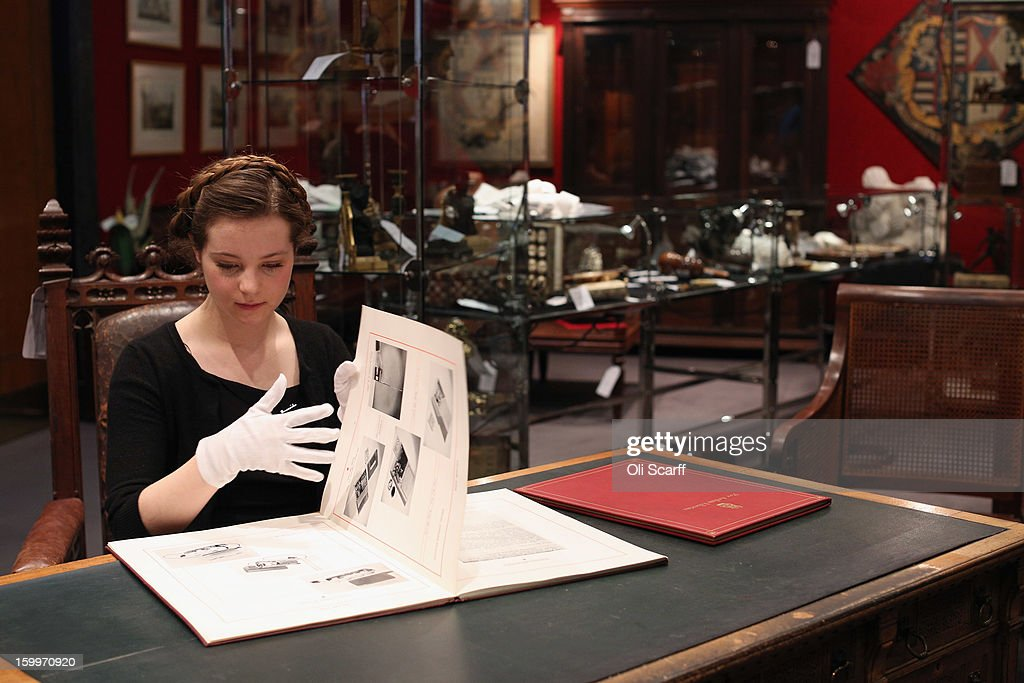 A gallery assistant at Bonhams auction house admires a MI9 spy catalogue from WWII containing top secret designs for covert equipment , which is expected to fetch 800 GBP in their forthcoming 'Gentleman's Library Sale', on January 24, 2013 in London, England. The auction includes an eclectic mix of rare items such as a a cigar that belonged to Winston Churchill and a pygmy hippo skeleton. It will take place in Bonhams Knightsbridge on January 29 and 30, 2013.