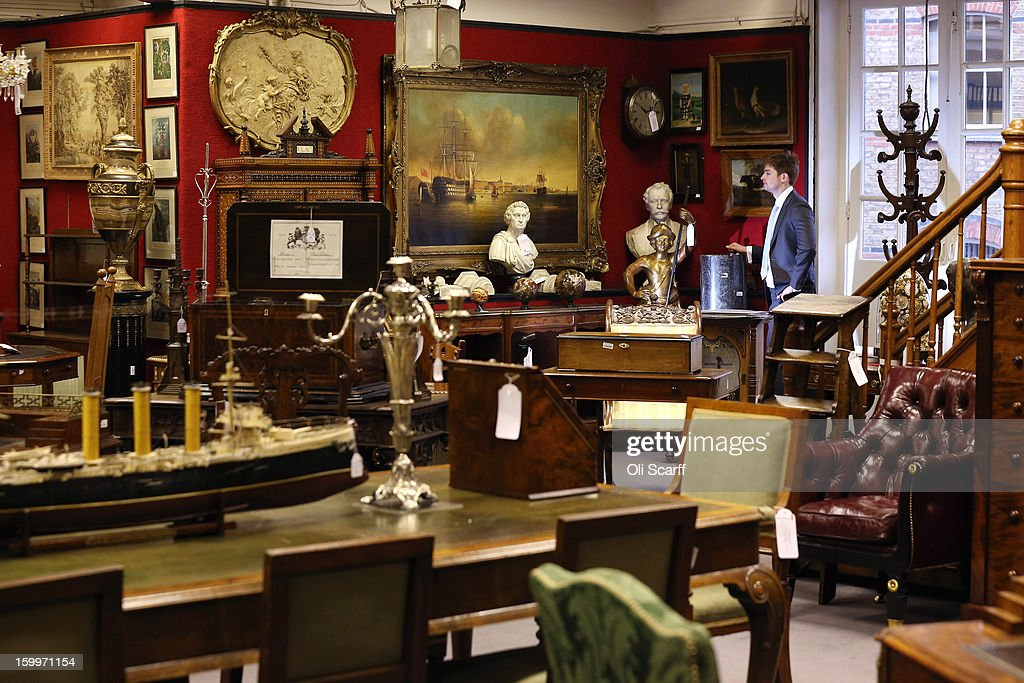 A gallery assistant at Bonhams auction house admires the lots for sale in their forthcoming 'Gentleman's Library Sale' on January 24, 2013 in London, England. The auction includes an eclectic mix of rare items such as a pygmy hippo skeleton, a cigar that belonged to Winston Churchill and a MI9 spy catalogue. It will take place in Bonhams Knightsbridge on January 29 and 30, 2013.