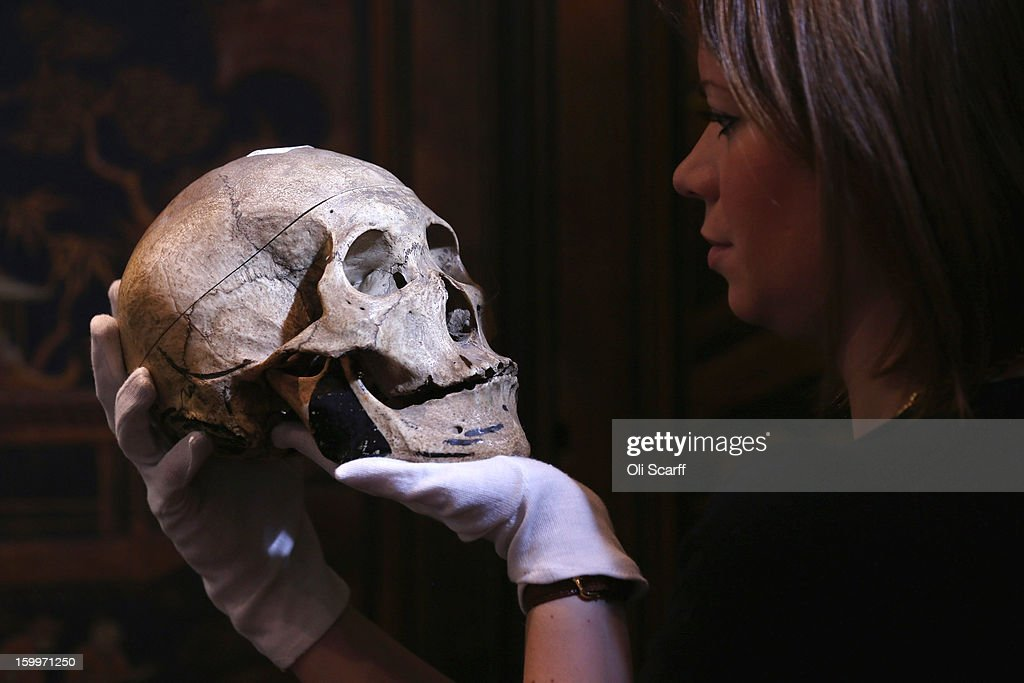 A gallery assistant at Bonhams auction house holds an engraved human skull, which is expected to fetch 900 GBP in their forthcoming 'Gentleman's Library Sale', on January 24, 2013 in London, England. The auction includes an eclectic mix of rare items such as a pygmy hippo skeleton, a cigar that belonged to Winston Chuchill and a MI9 spy catalogue. It will take place in Bonhams Knightsbridge on January 29 and 30, 2013.