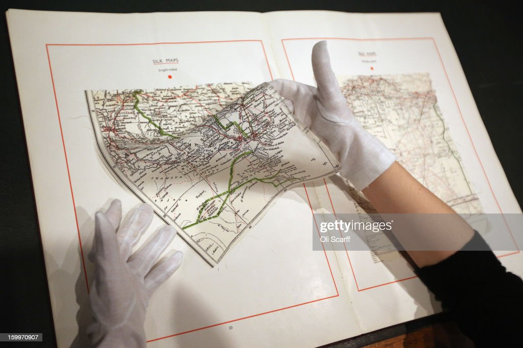 A gallery assistant at Bonhams auction house shows a MI9 spy catalogue from WWII containing top secret designs for covert equipment, which is expected to fetch 800 GBP in their forthcoming 'Gentleman's Library Sale', on January 24, 2013 in London, England. The auction includes an eclectic mix of rare items such as a cigar that belonged to Winston Churchill and pygmy hippo skeleton. It will take place in Bonhams Knightsbridge on January 29 and 30, 2013.