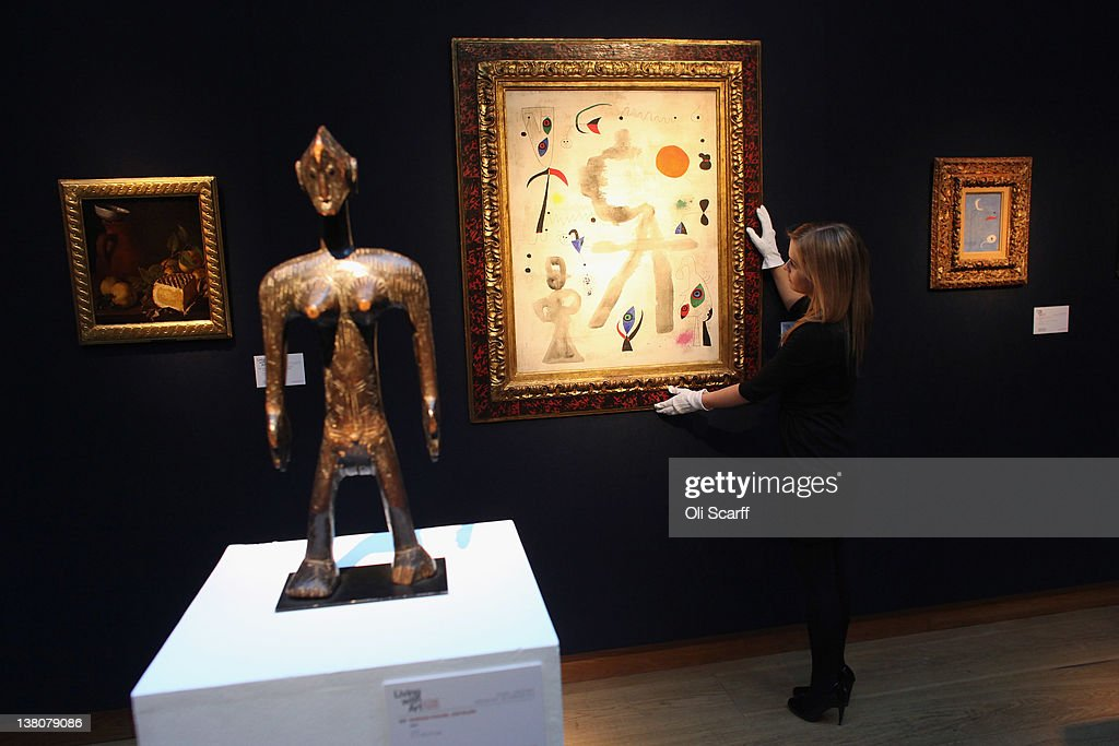 A gallery assistant at Christie's auction house adjusts a painting by Joan Miro entitled 'Personages et oiseaux devant le soleil' on February 2, 2012 in London, England. The artwork, which is estimated to fetch GBP £6 million is being auctioned in Christie's forthcoming sale 'Living With Art', which will take place on February 9 and February 10, 2012.