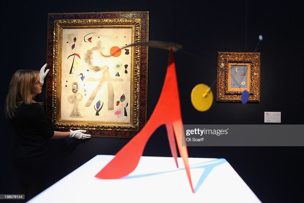 A gallery assistant at Christie's auction house adjusts a painting by Joan Miro entitled 'Personages et oiseaux devant le soleil' on February 2, 2012 in London, England. The artwork, which is estimated to fetch 6 million GBP, is being auctioned in Christie's forthcoming sale 'Living with Art' which will take place on February 9, 2012 and February 10, 2012.