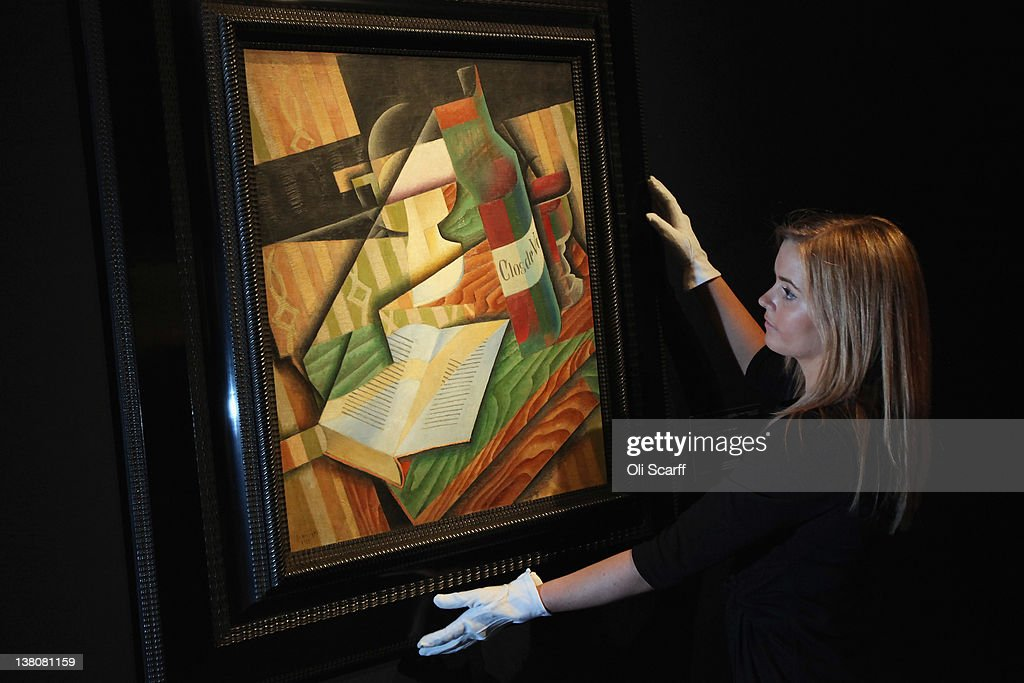 A gallery assistant at Christie's auction house adjusts a painting by Juan Gris entitled 'Le Livre' on February 2, 2012 in London, England. The artwork, which is estimated to fetch 18 million GBP, is being auctioned in Christie's forthcoming evening sales of 'Impressionist and Modern Art' and 'Art of the Surreal' which will take place between February 7, 2012 and February 9, 2012.