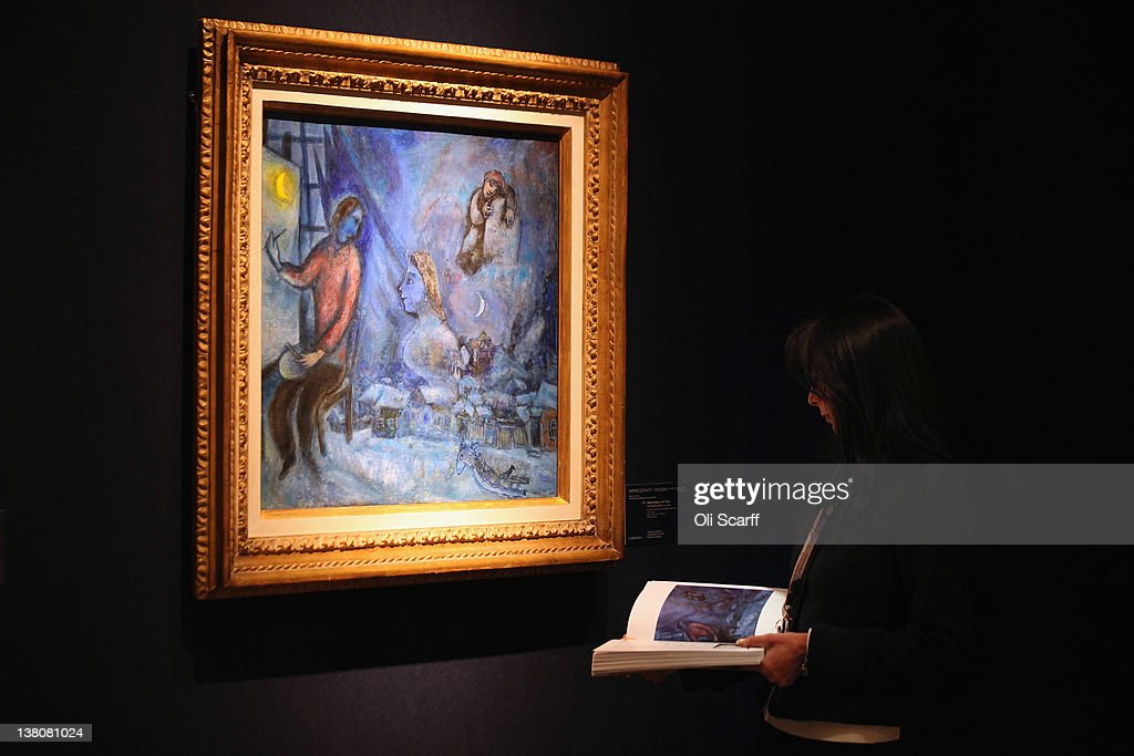A gallery assistant at Christie's auction house admires a painting by Marc Chagall entitled 'Hommage au passe, or La Ville' on February 2, 2012 in London, England. The artwork, which is estimated to fetch 800,000 GBP, is being auctioned in Christie's forthcoming sale 'Living with Art' which will take place on February 9, 2012 and February 10, 2012.