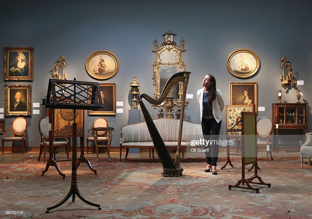 A gallery assistant at Christie's auction house admires a Regency double-action harp on September 16, 2013 in London, England. The work, which is expected to fetch 4,000 GBP, features in Christie's forthcoming sale of 'The Collection of Professor Sir Albert Richardson' which will be held on September 18 and 19, 2013. Over 650 lots owned by Sir Albert Richardson, a collector, architect and President of the Royal Academy between 1954-1956, are expected to collectively fetch over 4 million GBP. The eclectic auction includes: Old Master paintings, British watercolours, architectural drawings, English and European furniture, sculpture, garden statuary, books, clocks, musical instruments and Georgian costume.