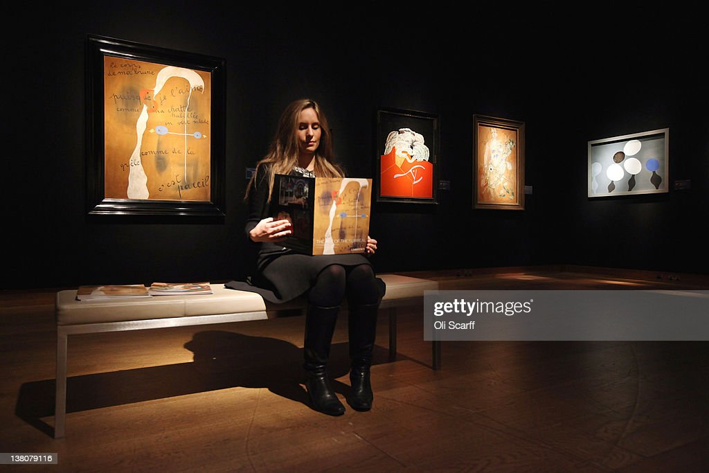 A gallery assistant at Christie's auction house sits in front of a painting by Joan Miro entitled 'Painting-Poem' (L) on February 2, 2012 in London, England. The artwork, which is estimated to fetch GBP £9 million, is being auctioned in Christie's forthcoming evening sales of 'Impressionist and Modern Art' and 'Art of the Surreal' which will take place between February 7 and February 9, 2012.