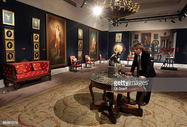 A gallery assistant at Sotheby's auction house examines a statue included in the forthcoming sale of furniture and works of art owned by Gianni...