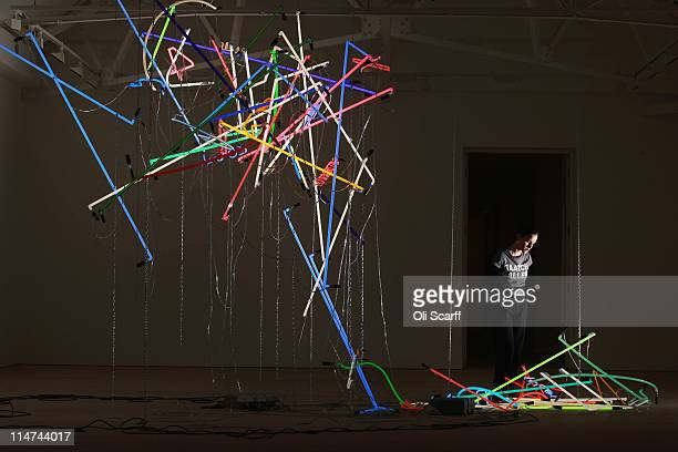 A gallery assistant at the Saatchi Gallery admires a sculpture by artist David Batchelor on May 26 2011 in London England The sculpture features in...