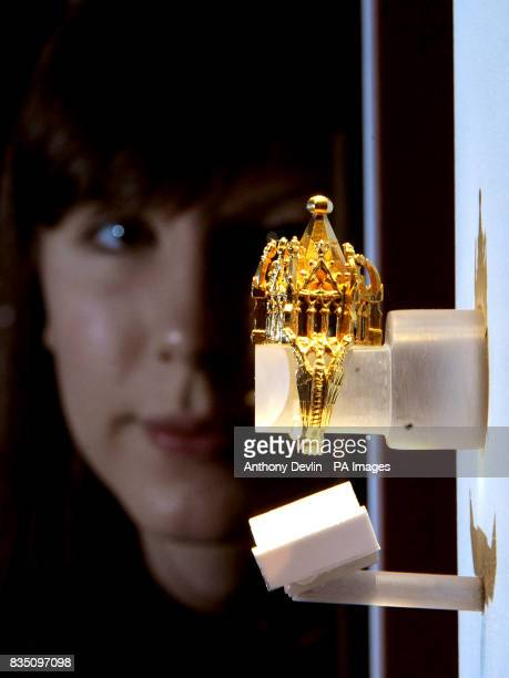 Gallery assistant Beth Humphries inspects a 14th century gold Jewish wedding ring during a preview for the forthcoming exhibition Treasures of the...