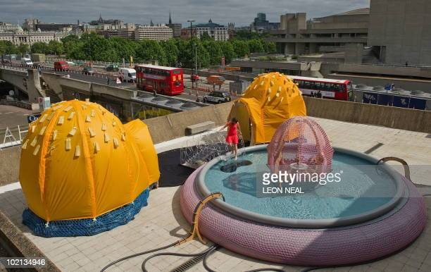 A gallery assistant dips her toe into the outdoor pool installation entiled 'H2OSfLv' by Brazilian artist Ernesto Neto at the Hayward Gallery in...