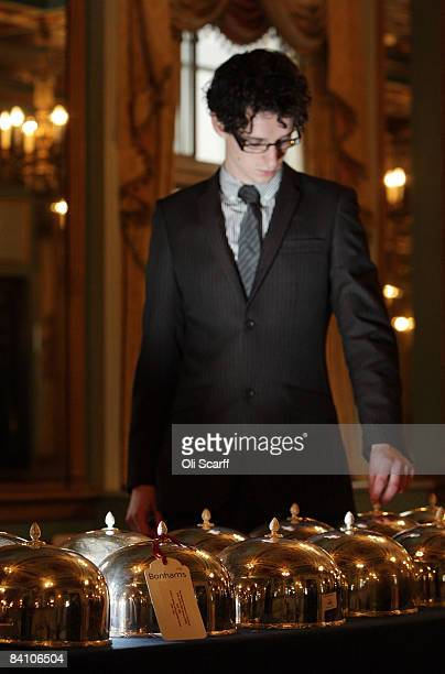 A gallery assistant for Bonhams auctioneers adjusts one of a set of 16 silver plated cloches at the Cafe Royal on Regent Street on December 22 2008...