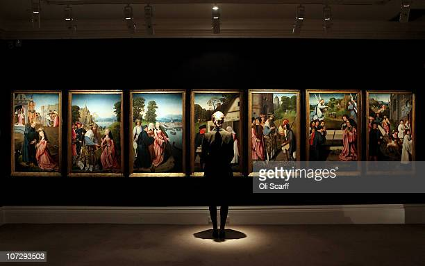 A gallery assistant for Sotheby's auction house admires 'Seven Scenes from the Life and Veneration of Saint Dymphna' by Goswijn van der Weyden which...