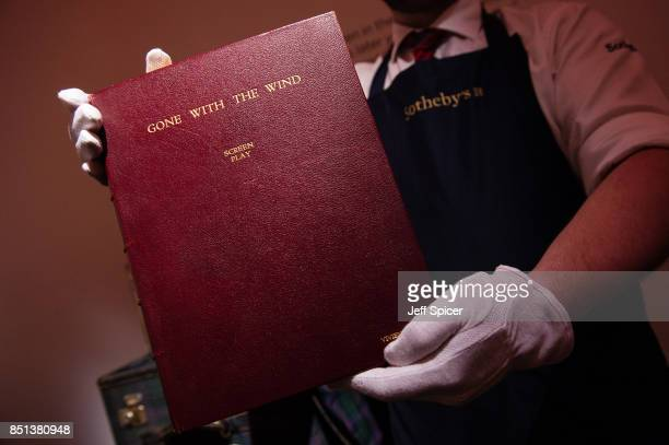 A gallery assistant holds Vivien Leigh's personal copy of Gone with the Wind film script during the press call for the Vivien Leigh auction at...