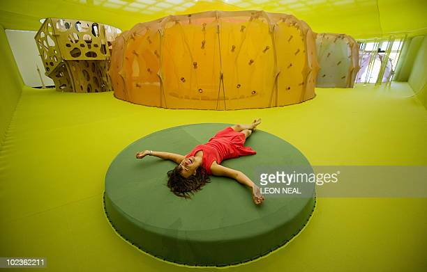 A gallery assistant lays on a platform within 'Horizonmembranenave' by Brazilian artist Ernesto Neto at the Hayward Gallery in central London on June...