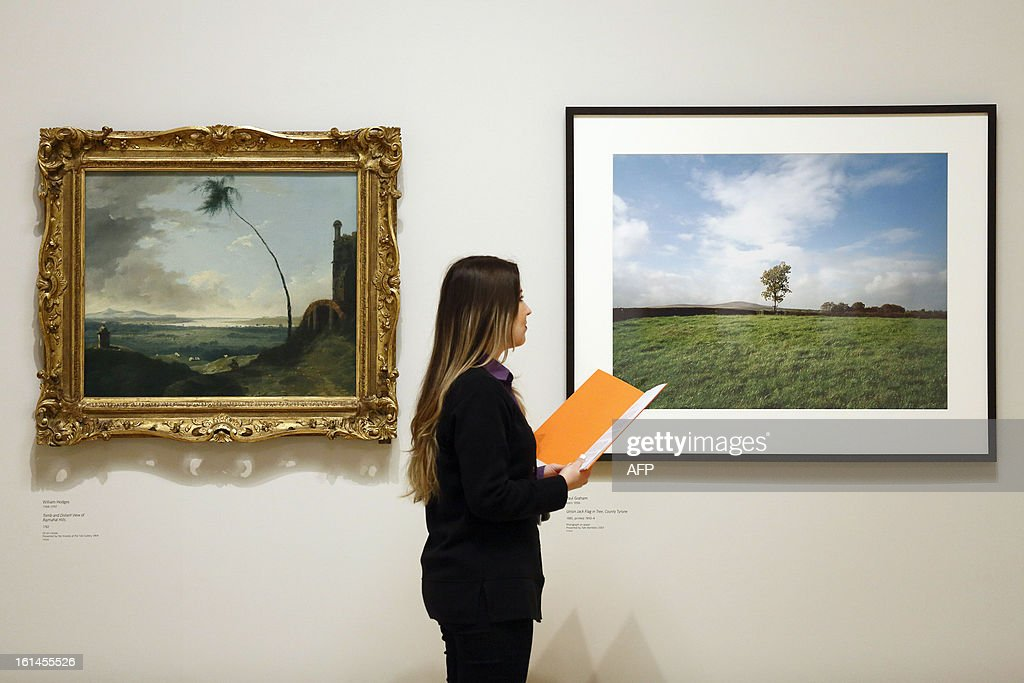 A gallery assistant looks at a photograph (R) entitled 'Union Jack Flag in Tree' County Tyrone (1985) by photographer Paul Graham and (L) 'Tomb and Distant View of Rajmahal Hills' (1782) by William Hodges at the 'Looking at the View' exhibition at Tate Britain in London on February 11, 2013. The display 'Looking at the View' pairs historical and contemporary works by artists spanning 300 years of British art, from JMW Turner and William Hodges to Tracey Emin and Julian Opie.