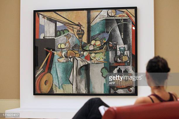 A gallery assistant looks at the painting 'La desserte' by French artist Henri Matisse at the Matisse Museum on June 20 2013 in Nice southeastern...