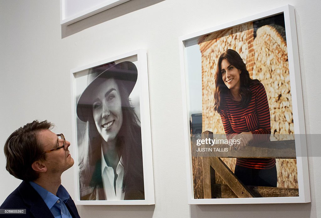 A gallery assistant looks at two new portraits of Catherine, Duchess of Cambridge, taken in the Norfolk Countryside by British photographer Josh Olins, at the Vogue 100: A Century of Style exhibition at the National Portrait Gallery in London on May 1, 2016. / AFP / JUSTIN
