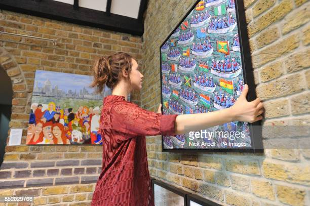 Gallery assistant Polly Millner prepares art works as more than fifty works of art inspired by the Thames Diamond Jubilee River Pageant go on free...