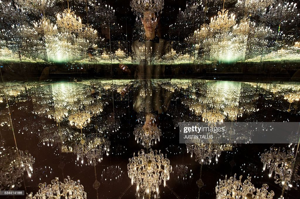 A gallery assistant poses for as photograph with an art installation entitled 'Chandelier of Grief', 2016, by Japanese artist Yayoi Kusama, at the Victoria Miro gallery in London on May 26, 2016. The exhibition is set to run from May 25 to July 30. / AFP / JUSTIN