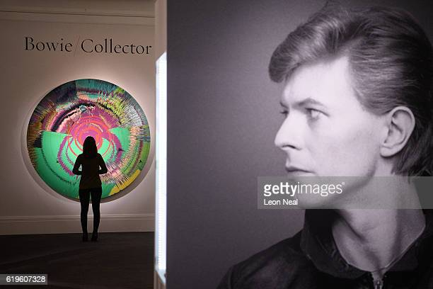 A gallery assistant poses with 'Beautiful Hallo SpaceBoy Painting' by Damien Hurst with David Bowie during the press preview of the 'Bowie/Collector'...