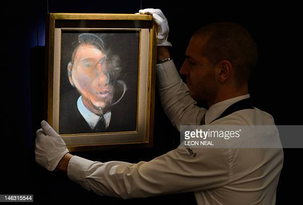 A gallery assistant poses with British artist and scientist Francis Bacon's 'Study for SelfPortrait 1980' at Sotheby's acution house in central...