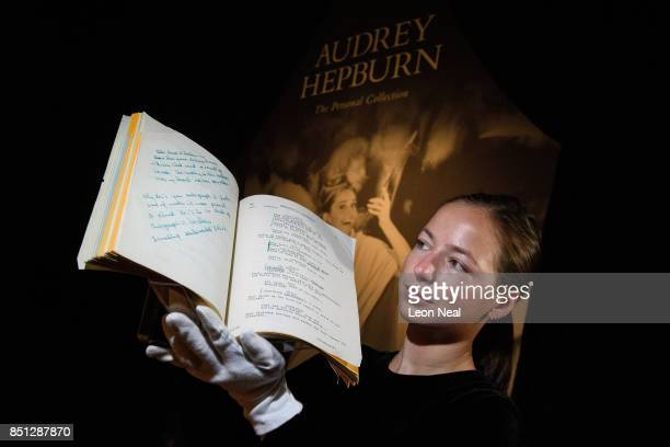 A gallery assistant poses with the working script for the film 'Breakfast at Tiffanys' during a preview of items from the sale of actrees Audrey...