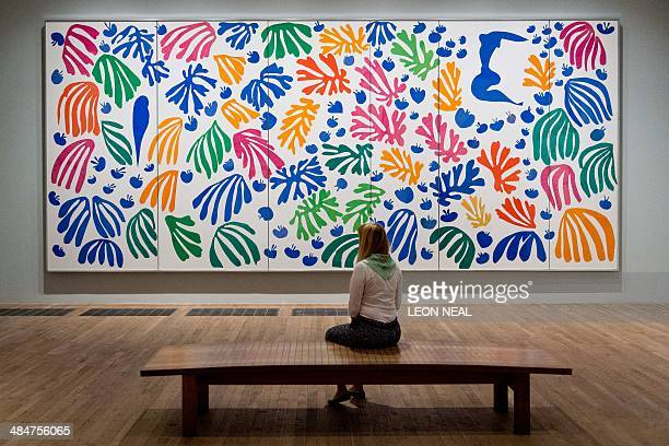 A gallery assistant sits in front of 'The Parakeet and the Mermaid' by Henri Matisse at the 'Henri Matisse The CutOuts' exhibition at the Tate Modern...