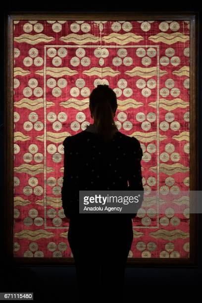 A gallery assistant views a large and exceptional Ottoman voided silk velvet and metalthread panel with cintamani and tigerstripe design Turkey late...