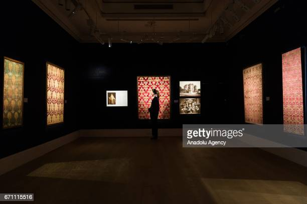 A gallery assistant views a selection of silk velvet textile panels from the collection of Argine Benaki Salvago showing at the London press view of...