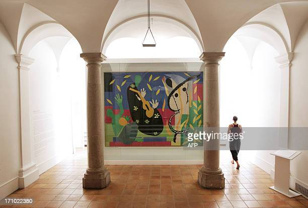 A gallery assistant walks near the painting 'La tristesse du roi' by French artist Henri Matisse at the Matisse Museum on June 20 2013 in Nice...