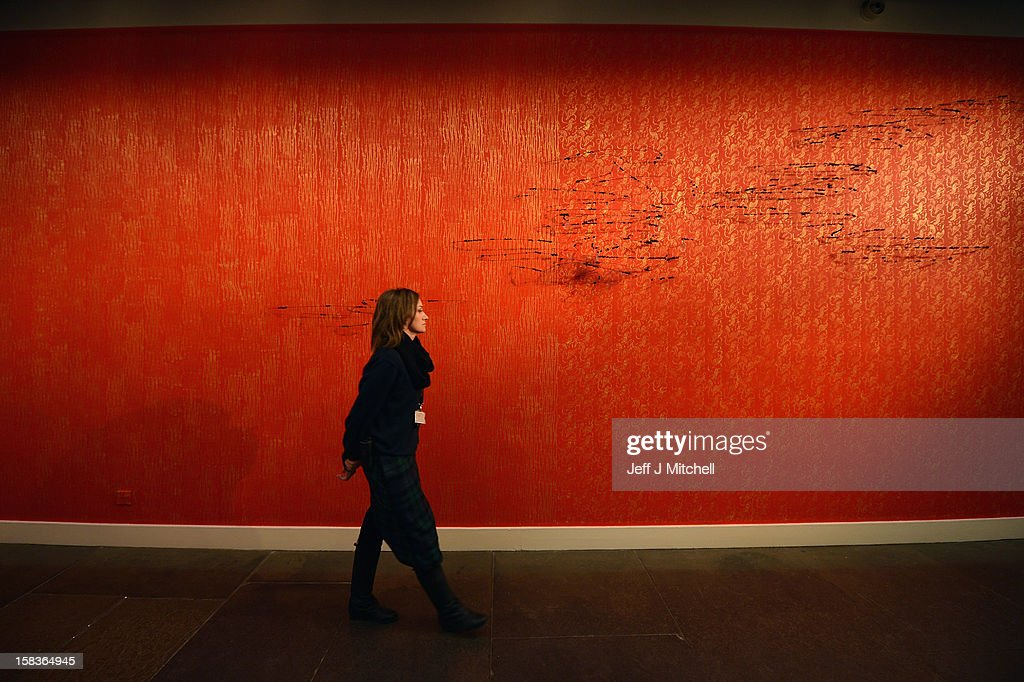 A gallery assistant walks past 'Untitled (from Flight Fantasy)' by David Hammons at The Scottish National Gallery of Modern Art on December 14, 2012 in Edinburgh, Scotland. The gallery has announced a major exhibition running from the 15th of December to the 8th of September 2013, bringing together works from the D. Daskalopoulos Collection, one of the most important collections of contemporary art with major works from the Scottish national collection. The innovative exhibition, curated by Keith Hartley, Chief Curator at the Scottish National Gallery of Modern Art, comprises over 120 works and will create a new and dynamic context for both collections.