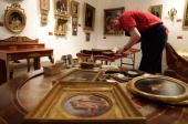 Gallery assistants at Sotheby's auction house hang paintings ahead of the forthcoming sale of furniture and works of art owned by Gianni Versace on...