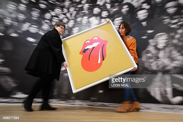 Gallery assistants pose for pictures with John Pasche's 1971 'Tongue and Lip Design' logo commissioned by Mick Jagger at a photocall for a...