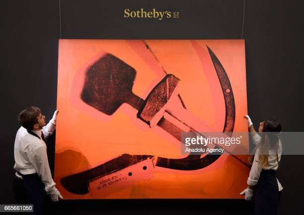 Gallery assistants pose with Andy Warhol Hammer and Sickle 1976 at the London press view of Impressionist Modern and Contemporary Art at Sotheby's on...