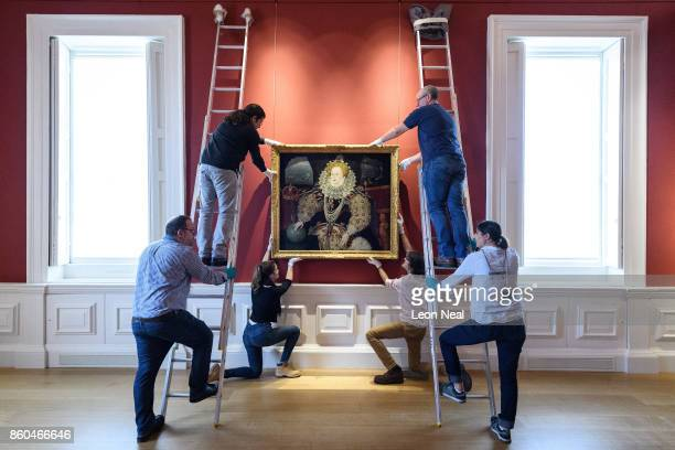Gallery assistants pose with the 'Armada Portrait of Elizabeth I' oil painting as it is unveiled following extensive cleaning at the Queen's House...